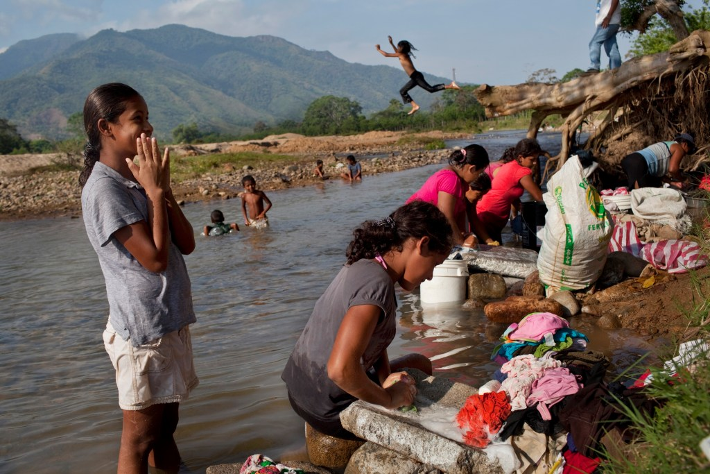 "In this May 6, 2012 photo, women wash clothes in a river near ""La Confianza"" peasant model city, Bajo Aguan, Honduras. Peasants from MUCA (Movimiento Unificado Campesino del Bajo Aguan) occupied around 7000 sq meters of productive land close to the city of Tocoa in the Valley of Bajo Aguan, eastern coast of Honduras in December, 2009. They operate a comercial production of african palm and they also stablished what they call a ""peasant model city"" called ""La Confianza"" where more than 300 hundred families live. Since then an open conflict between them and the alleged owner of the land, Miguel Facussé, one of the most powerful businessmen in Honduras has left more than 60 people dead including peasants, security guards, a journalist and members of the Honduran national police. (AP Photo/Rodrigo Abd)"