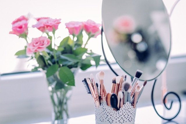 Fuss About Valentine's Day Desk With Pink Flowers in a vase and Makeup brushes and utensils in a holder, makeup mirror on the side, purposefulhabits