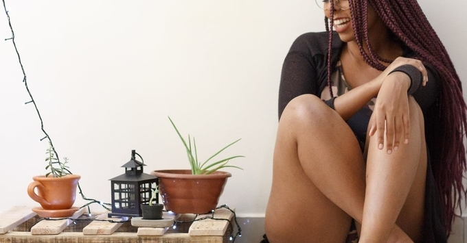 Woman with long braided hair sitting next to aloe vera plants, happy, simplify life