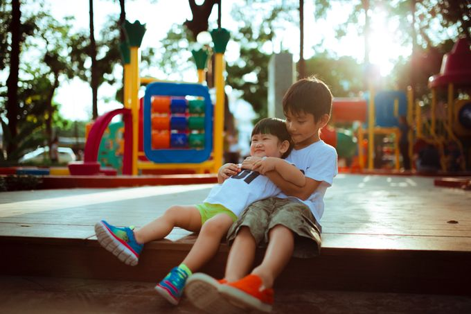 two boys playing on playground and hugging, best friends or brothers