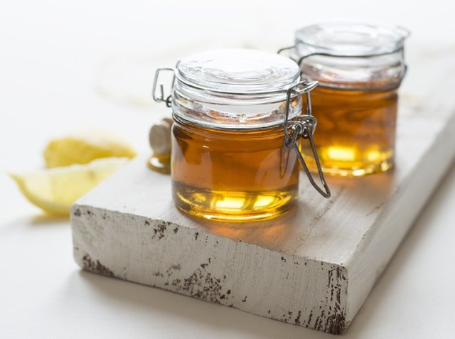two jars of honey, two slices on lemon on a white background table, hermetic jars, one day beauty detox, purposeful habits