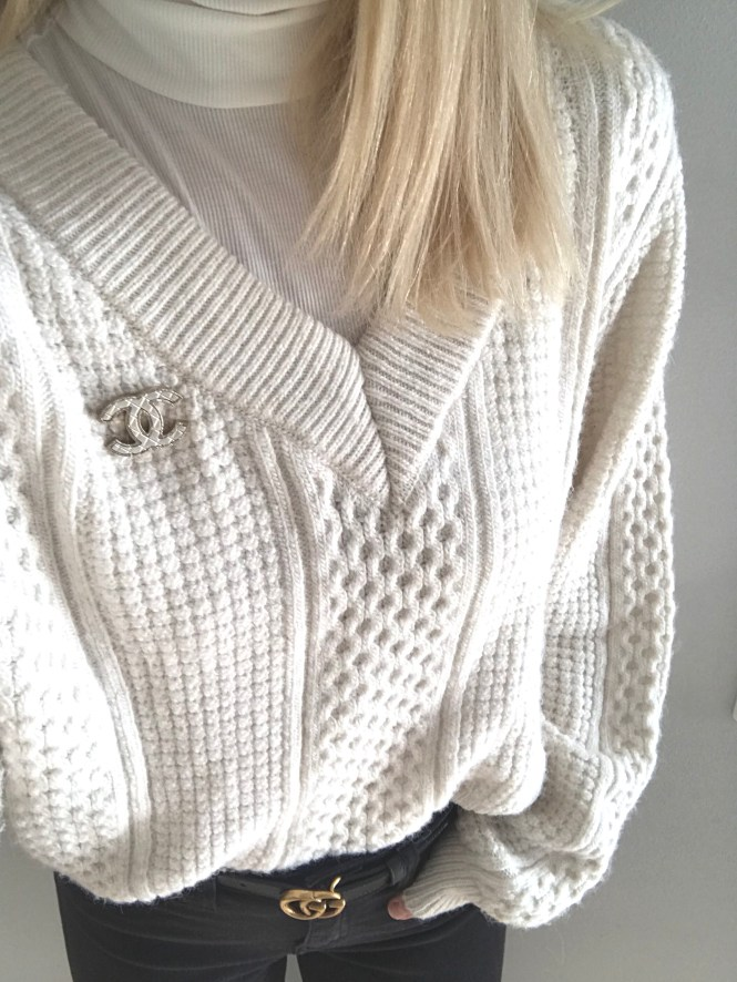 Chanel brooch and Gucci Marmont belt with a chunky white knit sweater.