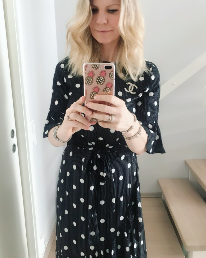 Wearing a black and white polkadot dress with a Chanel brooch.