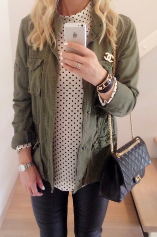 Wearing a military green utility jacket, black and white polkadot top, a Chanel brooch and Chanel 226 Reissue flap bag.