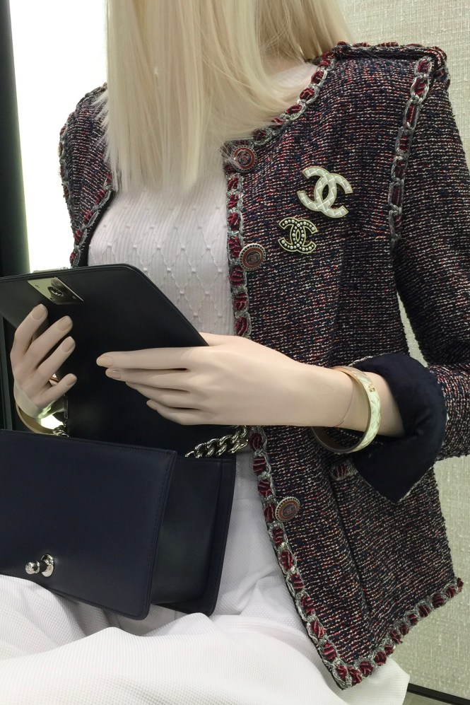 Chanel brooches on a Chanel jacket in a Chanel boutique.