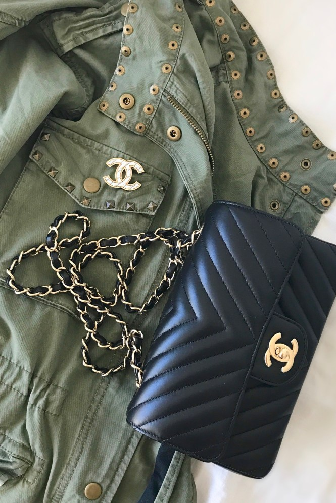 Military green utility jacket with a Chanel brooch and Chanel chevron mini rectangular bag.