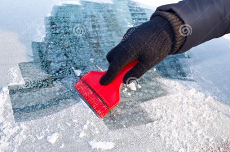 Membersihkan lapisan es di kaca mobil saat winter.