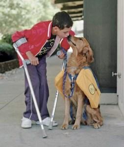 Child using crutches kissing dog