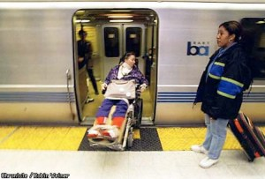Jean Nandi maneuvers her wheelchair onto a BART train -- just one woman with a disability who regularly used BART for transportation before the strike.  An unidentified woman waits to board at the 19th Street BART station in Oakland.  Photo by Robin Weiner/The Chronicle