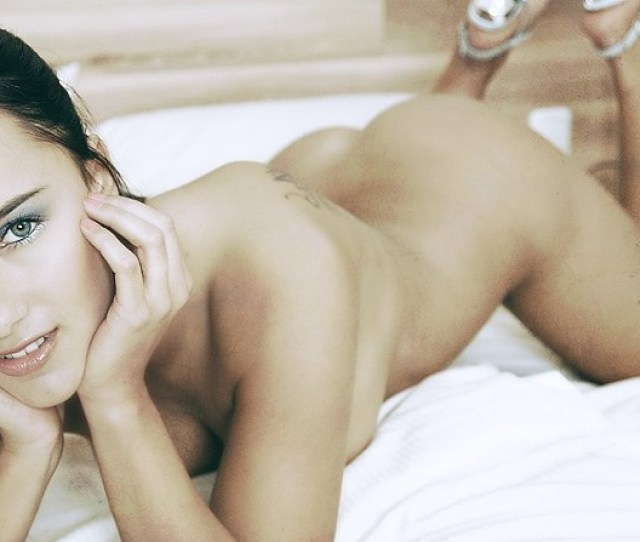 A Naked Woman With Back Tattoo Lying On Her Bed