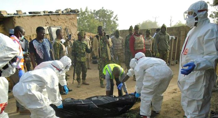 Rescued workers collect bodies following an attack by Boko Haram suicide bombers at the outskirts of Maiduguri, Nigeria, Friday