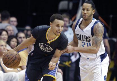 El base de los Warriors de Golden State, Stephen Curry, es defendido por el base de los Mavericks de Dallas, Devin Harris, durante la segunda mitad del juego de NBA del sábado 4 de abril de 2015 en Dallas. (Foto AP/LM Otero)