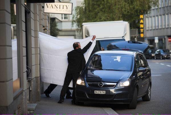 en un intento de privacidad, una cortina blanca cubre la vía de un funcionario mientras lo escoltan a un auto oficial (foto cortesía AP)