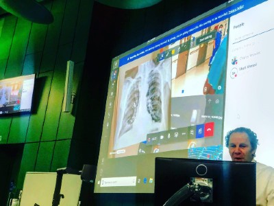 The live feed is displayed on the projector in the lecture theatre, complete with the patient's x-ray images