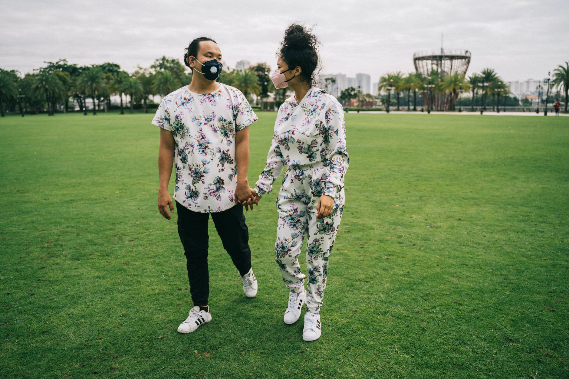 couple with face masks standing on green grass field