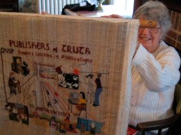 "Mar­jorie Ewbank holds up QUIP's ""Quaker Tapestry"":http://www.Quaker-tapestry.co.uk panel, which should be fin­ished by the end of the cen­tury."
