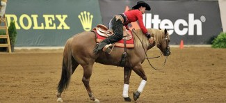 Ann Poels gives her chestnut Quarter Horse stallion a hug after their high scoring run.