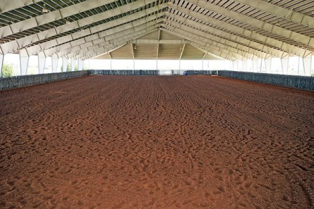 A huge covered arena of 135×359 (48,465 ft.) with three cattle holding pens, large staging area, return alley, roping setup, and an impressive Mexican tile roof.