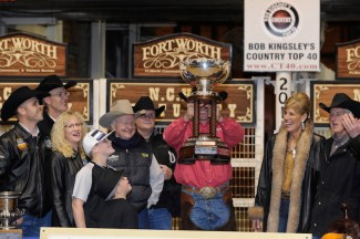 People holding up the NCHA futurity cup an award that comes with great prestige
