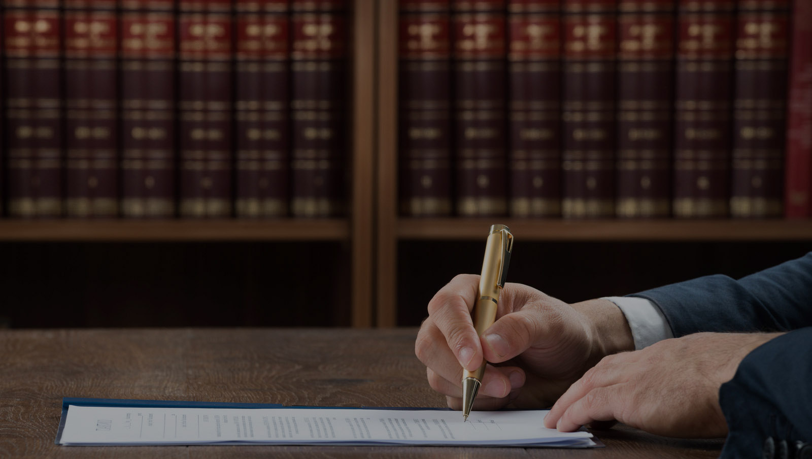 Lawyer signing an agreement in front of legal books