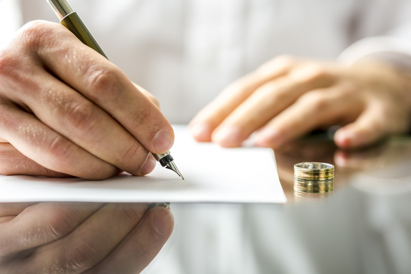 Close up of hand signing a separation agreement with wedding band on table