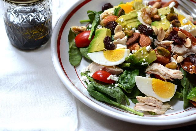This unique version of cobb salad uses goat cheese and prosciutto instead of blue cheese and bacon. Trail mix as a salad topper makes it extra delicious. | QueenofMyKitchen.com