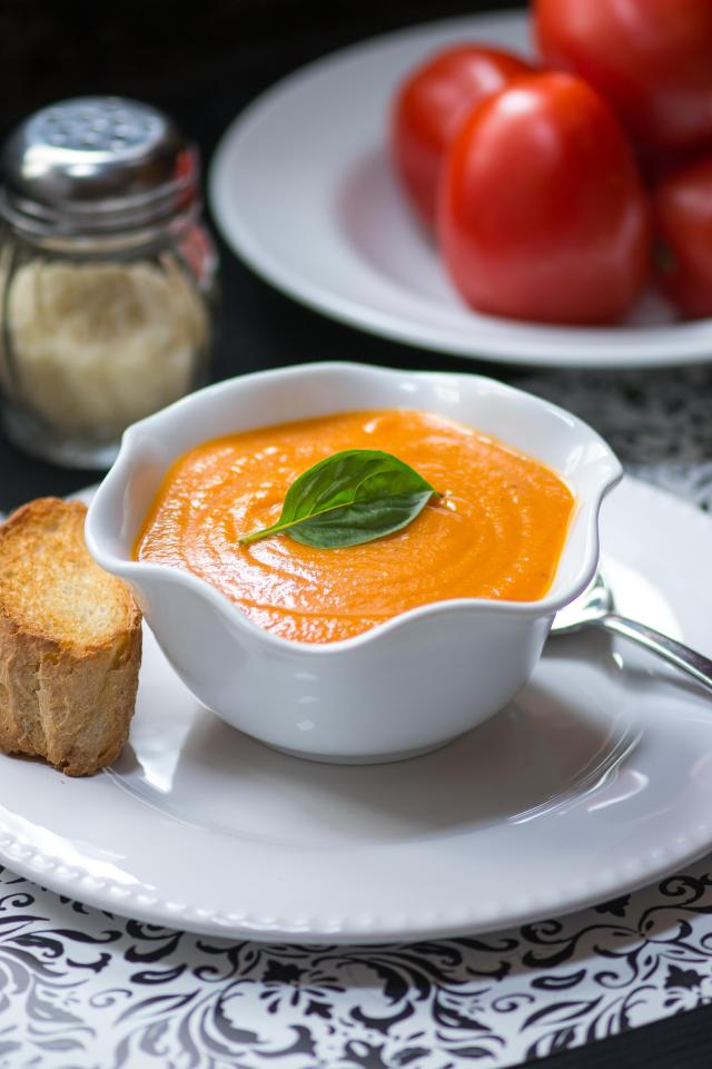 Roasted Garlic Cream of Tomato Soup. A lightened up version of the classic soup that is thickened with yukon gold potatoes and infused with sweet, mellow, roasted garlic. | QueenofMyKitchen.com