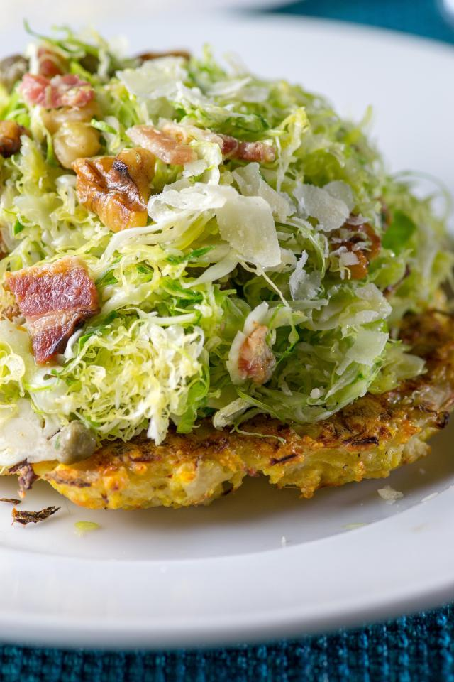 Shaved Brussels Sprouts Over Crispy Cauliflower Cakes - Thinly sliced Brussels sprouts slaw served over crispy cauliflower cakes, dressed in a lemon vinaigrette and topped with bacon and walnuts. A sensational salad made from two vegetables once considered boring and unglamorous! | QueenofMyKitchen.com