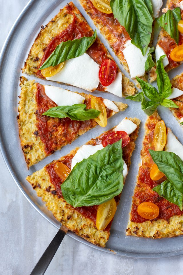 Cauliflower Broccoli Pizza Crust - Get a healthy dose of veggies with this delicious, gluten-free pizza crust that contains no breadcrumbs and clocks in at only 80 calories per slice! This recipe doesn't require the messy job of squeezing the liquid out of the vegetables. |QueenofMyKitchen.com |#pizza #pizzacrust #glutenfreepizza #cauliflowerpizza #cauliflowerpizzacrust #vegetablepizzacrust #glutenfree #glutenfreerecipe