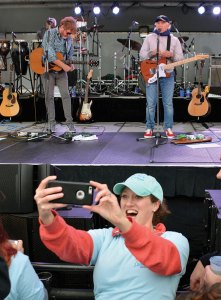 Person taking selfie with band playing in background