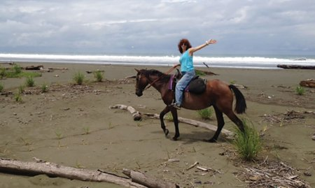 Nancy riding a horse on the beach