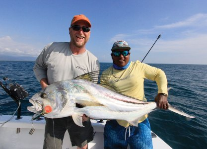Two men holding large roosterfish