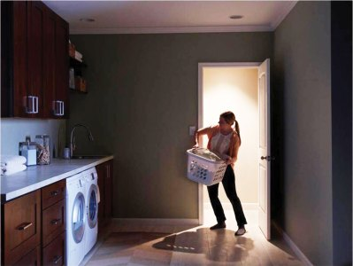 Woman trying to turn on lights while carrying laundry basket