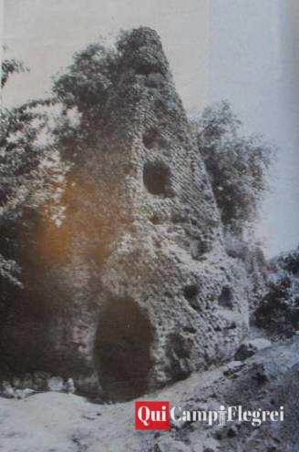 """Esterno del mausoleo a cuspide piramidale prima dello scavo del 1972, da """"Gruppo Archeologico Napoletano""""."""