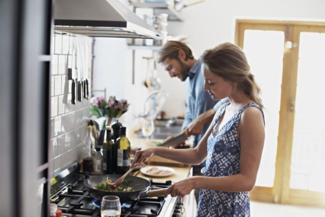 young couple cooking dinner