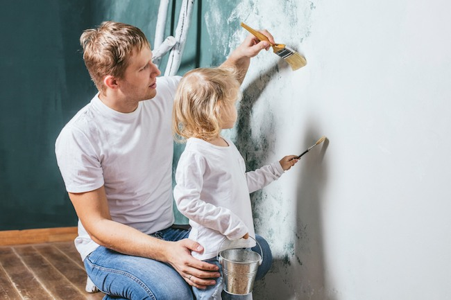 Father And Daughter Paint a wall in their home