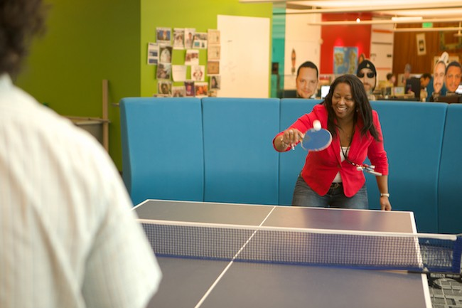 A young woman plays ping pong at work