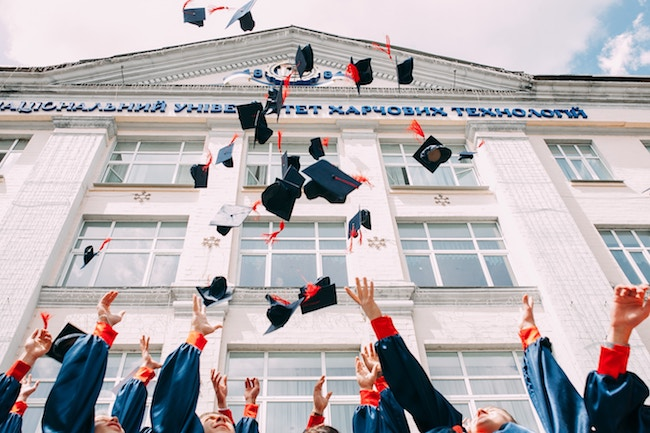Graduating class throwing hats