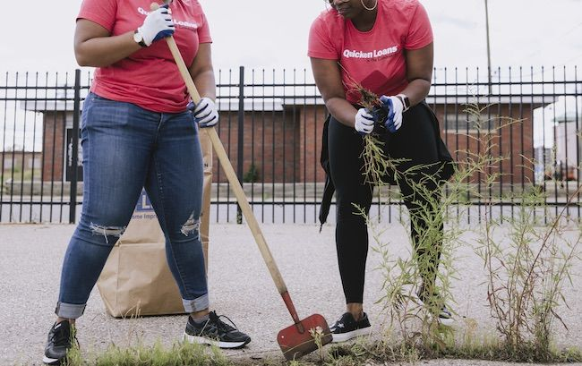 Two QL employees cleaning up a parking lot in Detroit.