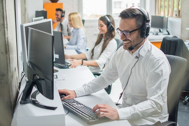 Man on computer with headset.