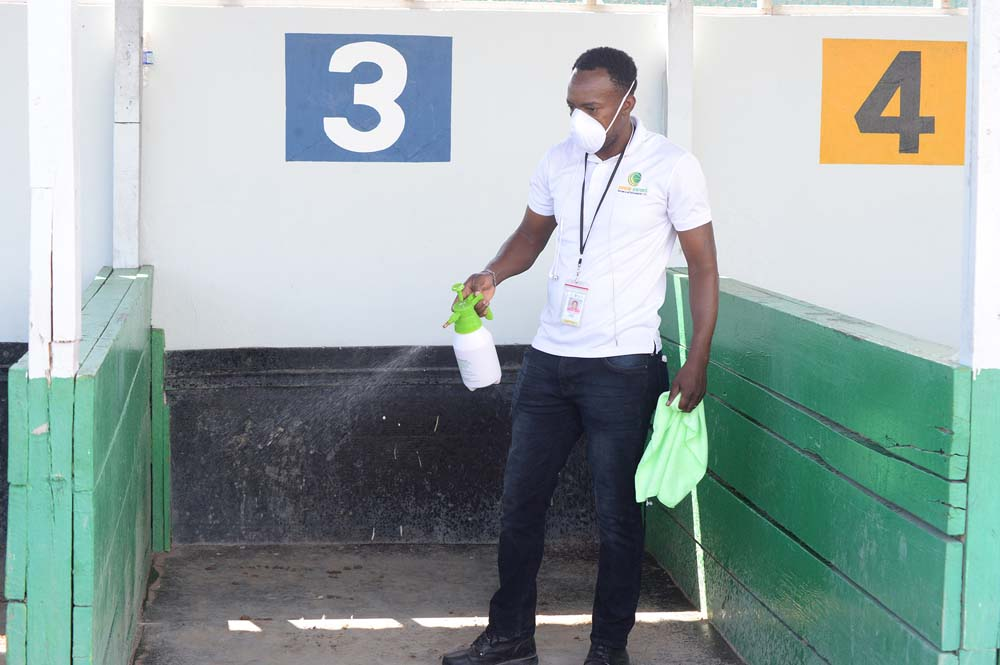 A team member of the promoting company sanitising the saddling barn area.