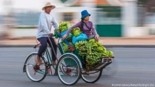 """عربة ريكشا في كمبوديا وهي دراجة مطورة عن عربة الجرّ الأصلية والتي يعود أصل اختراعها لليابانيين، وتعني كلمة ريكشا باليابانية """"عربة بقوة الإنسان"""". وتستخدم دراجة ريكشا ذات العجلات الثلاثة الكبيرة في العديد من البلدان كوسيلة نقل مريحة وسريعة. ولدراجة ريكشا نماذج مختلفة، ومقاعد الراكبين ممكن أن تكون في الأمام أو الخلف."""