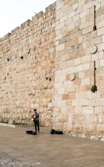 A lonely busker in the shadows of the Jerusalem city walls