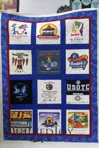 Barb shows off the finished T-shirt quilt she made during the T-shirt Quilt Camp at Quilted Joy