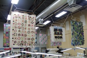 Quilts by Mary Bauer hanging in the Quilted Joy longarm studio
