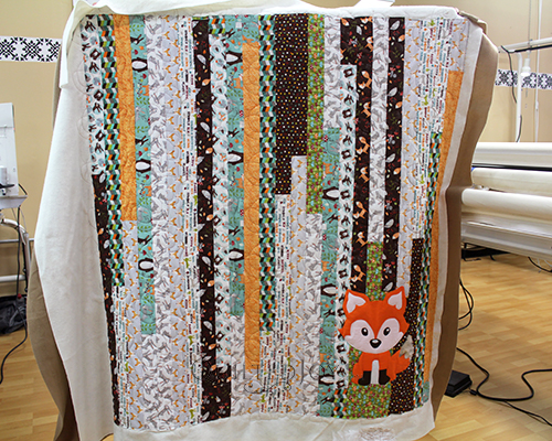 Judy's Jelly Roll Race quilt with an appliqued Fox!