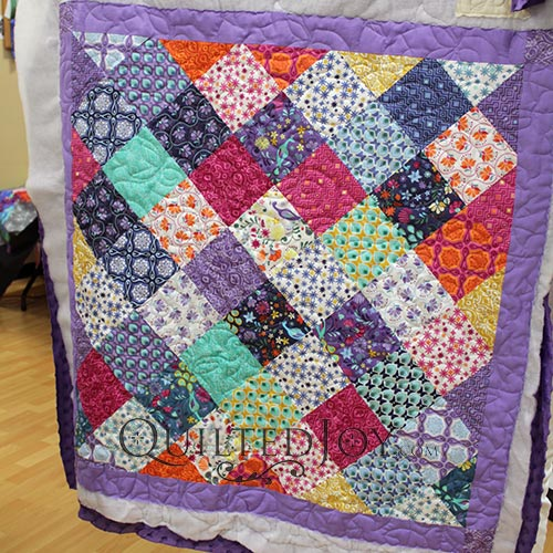 Sally's Charm Pack Quilt, quilting on a longarm quilting machine at Quilted Joy