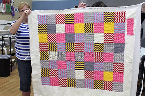 Carol's Layer Cake Zig Zag quilt after her longarm rental certification class at Quilted Joy
