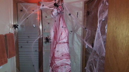 This hanging body in the bathroom is surrounded by spider webs for a terrifying and gruesome scene in your bathroom