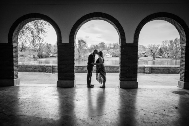 black and white silhouette engagement photo under archway